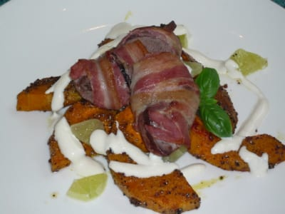 A dish of pigeon breast wrapped in bacon, served with a tahini dressing and roasted butternut squash