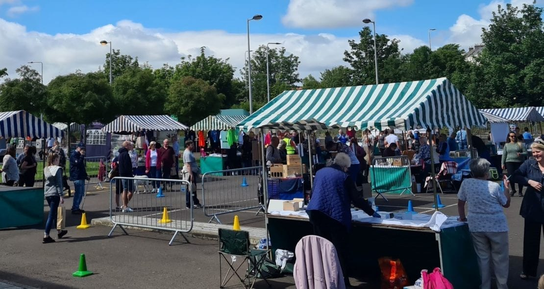 stalls and shoppers at the socially distant summer market